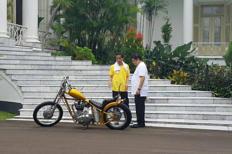 Presiden Joko Widodo memperlihatkan motor modifikasi bergaya chopperland miliknya kepada Menteri Perindustrian Airlangga Hartarto saat pertemuan di Istana Bogor, Sabtu (24/3/2018).