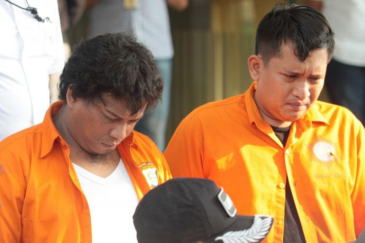 Dua orang tersangka kasus peluru nyasar ditunjukkan kepada wartawan saat keterangan pers pengungkapan kasus di Polda Metro Jaya, Jakarta, Selasa (16/10/2018). Polda Metrojaya berhasil mengungkap kasus peluru nyasar ke gedung DPR pada hari Senin (15/10) lalu dan mengamankan dua orang tersangka berinisial I dan R serta menyita dua pucuk senjata api beserta pelurunya. ANTARA FOTO/Reno Esnir/wsj.