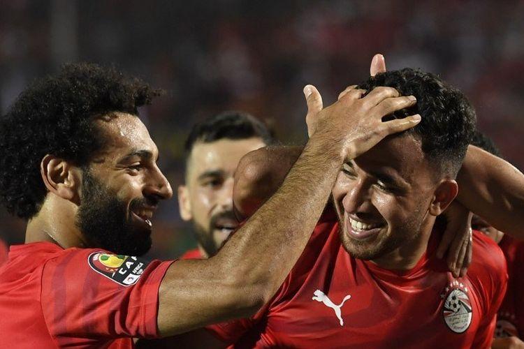 Mohamed Salah merayakan gol Trezeguet pada pertandingan Mesir vs Zimbabwe dalam partai pembuka Piala Afrika 2019 di Kairo, 21 Juni 2019.