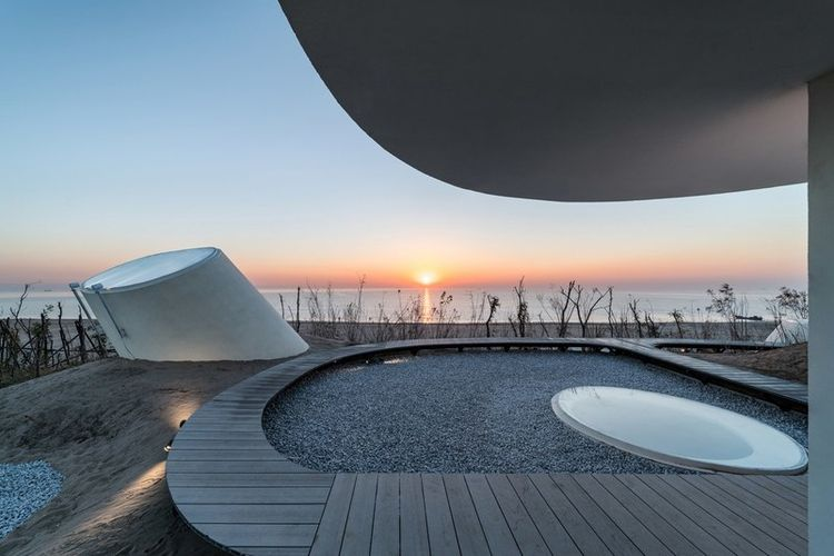 Ide untuk merancang bangunan di bawah permukaan bukit pasir datang dari firma OPEN Architecture.