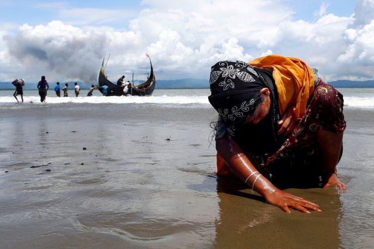 Seorang perempuan pengungsi Rohingya yang kelelahan menyentuh pantai setelah menyebrangi perbatasan Bangladesh-Myanmar dengan kapal melalui Teluk Bengal, di Shah Porir Dwip, Bangladesh, Senin (11/9). ANTARA FOTO/REUTERS/Danish Siddiqui/cfo/17
