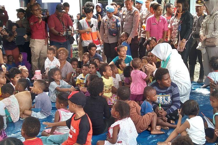 Istri Kapolri Tri Suswati Karnavian (baju putih) sedang bercenkrama dengan anak-anak pengungsi  yang ada di Posko Induk Sentani, Kabupaten Jayapura, Papua, Jumat (22/3/2019).