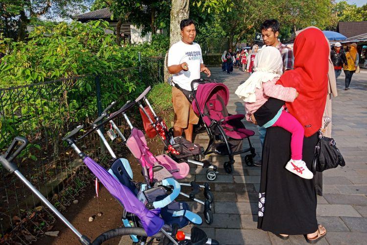 Salah satu keluarga sedang menawar persewaan stroller untuk balita yang tersedia di Candi Borobudur, Magelang, Jawa Tengah ,Sabtu (10/3/2018).