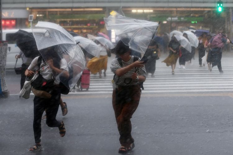 Warga Jepang berjalan di tengah angin kencang dan hujan deras saat Topan Jongari menerjang Tokyo pada akhir Juli 2018.