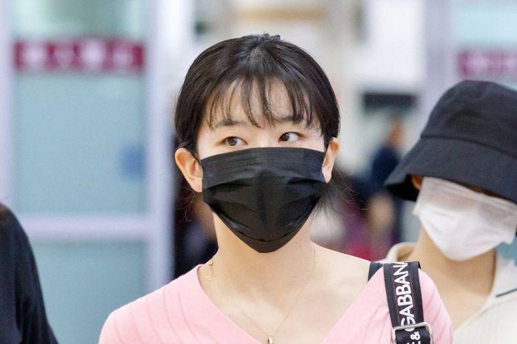 Bintang girlband Red Velvet, Seulgi saat berada di bandara dan mengenakan masker hitam di wajahnya.