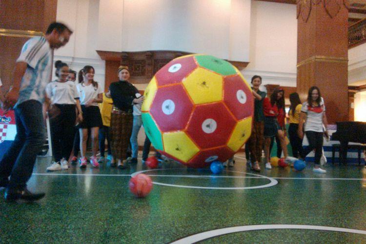 Karyawan dan karyawati The Sunan Hotel Solo, Jawa Tengah memakai jersay, beskap dan kebaya menggiring bola raksasa semarakkan babak delapan besar piala dunia 2018, Jumat (6/7/2018).