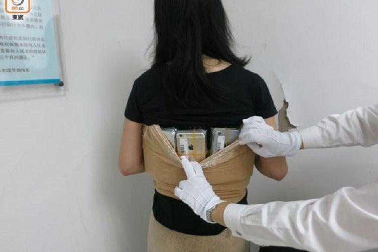 Seorang wanita menyelundupkan 102 iPhone dan 15 jam tangan bermerek Tissot dari Hongkong menuju China daratan dan tertangkap petugas Bea dan Cuka di perbatasan Shenzhen.