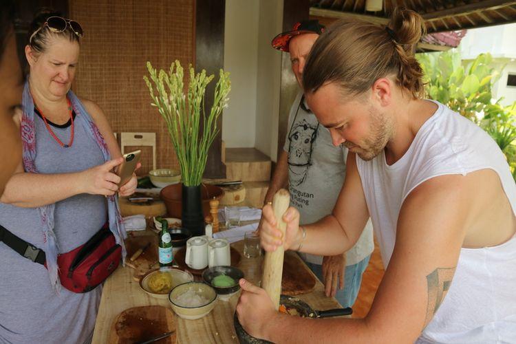 Wisatawan mancanegara mencoba memasak makanan bali di Ubud.