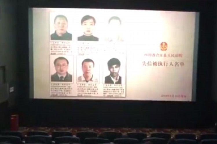 Wajah para pengutang dipajang di layar sebuah bioskop di Sichuan, China.