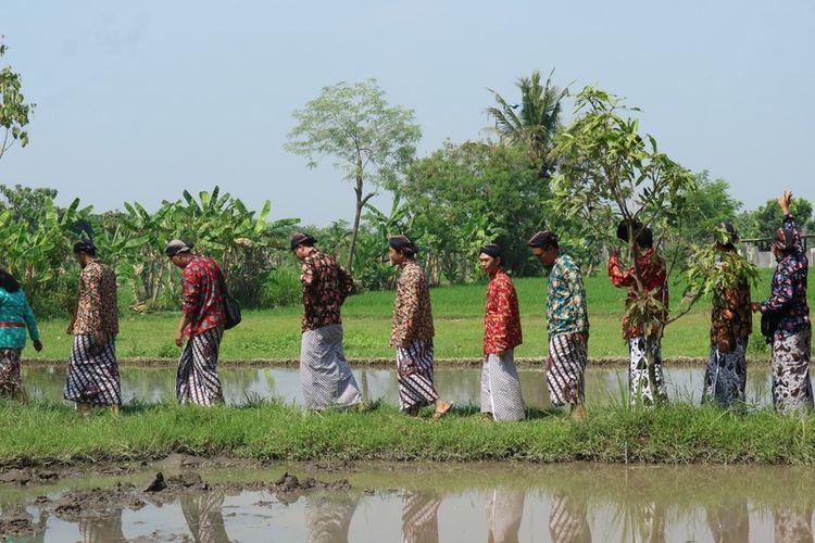 Tamu berbusana Jawa berjalan di sawah sekitar Omah Kecebong, Sleman, Yogyakarta.