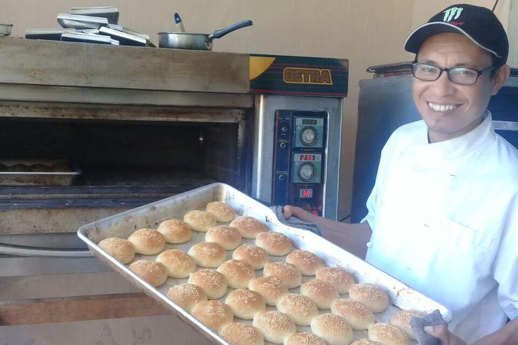Ferdy sedang menyelesaikan pesanan roti kompiang di kediamannya, Jalan Pulau Flores, Gang V Nomor 2, Denpasar, Bali, Jumat (6/4/2018).