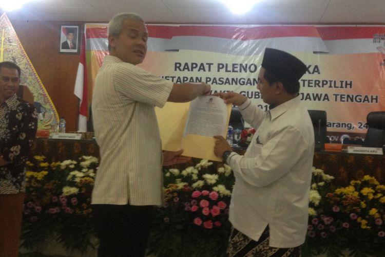 Ganjar Pranowo dan Taj Yasin memegang surat keputusan dari KPU Jawa Tengah seusai sidang pleno penetapan pasangan calon terpilih, Selasa (24/7/2018).