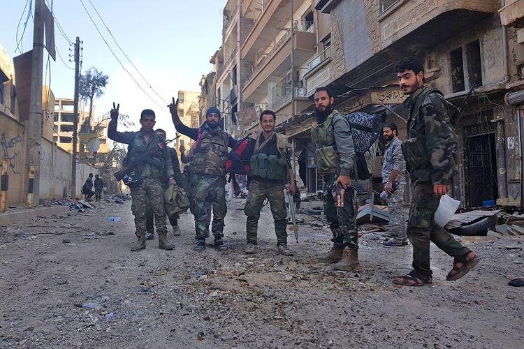 Para prajurit AD Suriah dan milisi pro-pemerintah berfoto di depan sebuah gedung yang rusak berat di kota Deir Ezzor pada 3 November 2017.