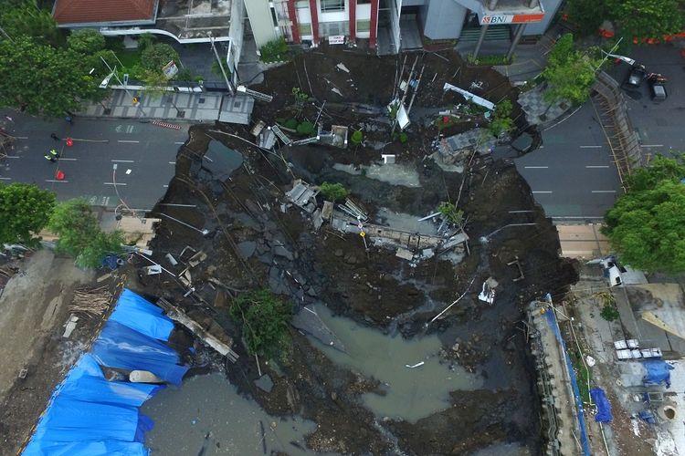 Foto aerial kondisi tanah ambles di Jalan Raya Gubeng, Surabaya, Jawa Timur, Rabu (19/12/2018). Jalan raya tersebut ambles sedalam sekitar 20 meter dengan lebar 30 meter pada Selasa (18/12/2018) malam diduga karena proyek pembangunan gedung di sekitar lokasi. ANTARA FOTO/Didik Suhartono/wsj.