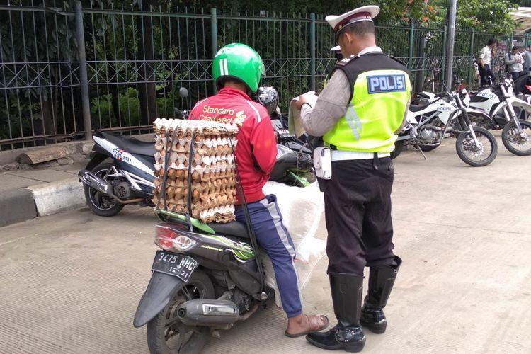 Sepeda motor membawa beban berlebih terjari Operasi Keselamatan Jaya di UKI, Jumat (9/3/2018)