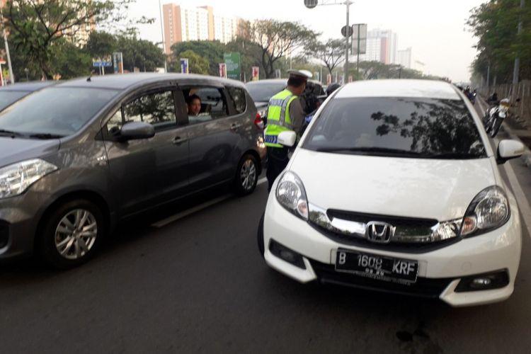 Polisi menghentikan mobil yang melanggar aturan ganjil-genap di Jalan Benyamin Sueb, Jakarta Utara, Rabu (1/8/2018).