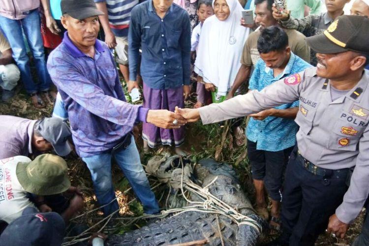 Warga menyerahkan buaya yang telah ditangkap kepada polisi di Desa Lhok Seuntang, Kecamatan Julok, Kabupaten Aceh Timur, Senin (13/2/2018).