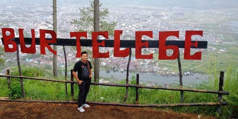 Wisatawan berfoto di depan papan nama obyek wisata Bur Telege, Kabupaten Aceh Tengah, Aceh, Kamis (24/7/2019).