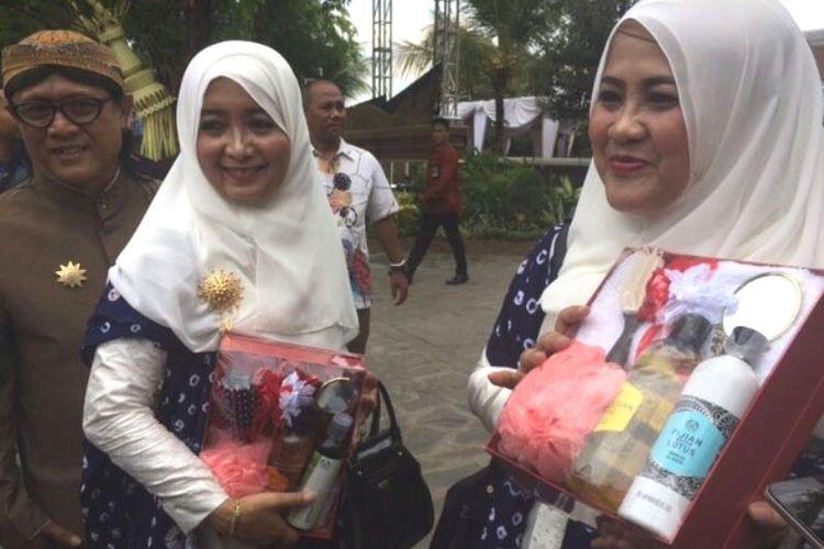Haryani (kanan), menunjukkan souvenir dari acara siraman Kahiyang Ayu di Solo, Jawa Tengah (7/11/2017).