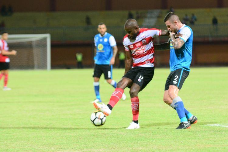 Striker Madura United, Greg Nwokolo, mencoba melewati hadangan bek Barito Putera dalam pertandingan uji coba.
