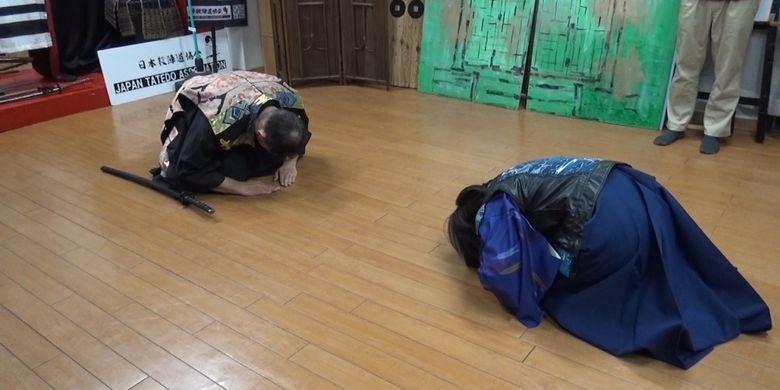 Duduk bersimpuh dan menundukkan kepala sambil mengatakan ?Yososhiku Onegaishimasu?.