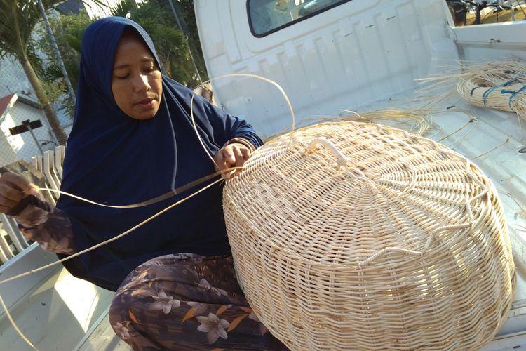 Ferdiyanti, seorang perempuan perajin rotan asal Desa Lamgaboh, Kecamatan Lhoknga, Aceh Besar, tengah menganyam rotan menjadi tudung saji.