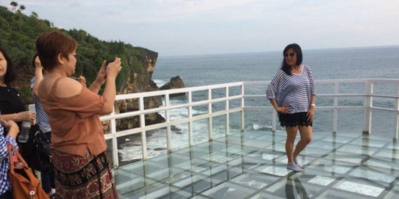 Pengunjung berfoto di teras Pantai Nguluran, Desa Girikarto, Kecamatan Panggang, Gunungkidul, DI Yogyakarta.