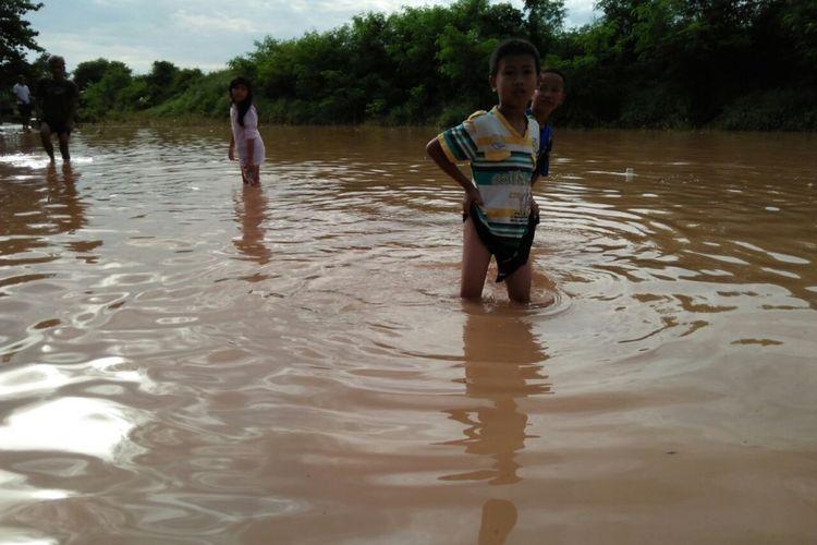 Anak-anak di Perum BMI,  Desa Dwuhan Tengah, Kecamatan Cikampek, Karawang,  Kamis (4/1/2018) melintas di area yang terendam banjir. Perumahan ini terendam sejak Rabu (3/1/2018) sore.