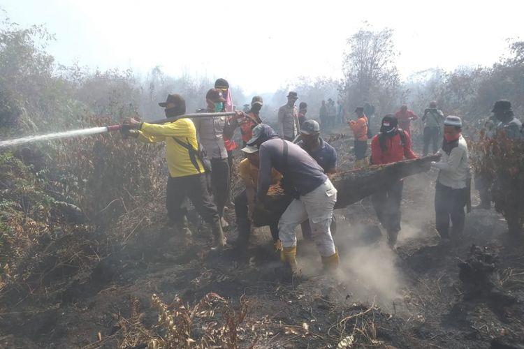 Tim Satgas Karhutla dan warga mengangkat kayu untuk dijadikan jembatan untuk melakukan pemadaman api yang membakar perkebunan karet masyarakat di Kelurahan Terkul, Kecamatan Rupat, Kabupaten Bengkalis, Riau, Jumat (22/2/2019).