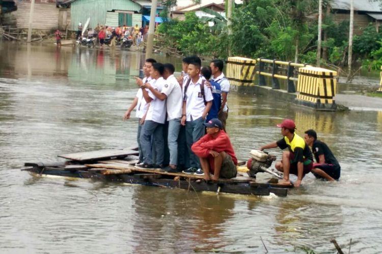 Siswa SMA 14 Ranomeeto Barat, Kabupaten Konawe Selatan, Sultra, terpaksa mengunakan rakit darurat untuk sampai ke sekolah karena jalan putus akibat banjir.