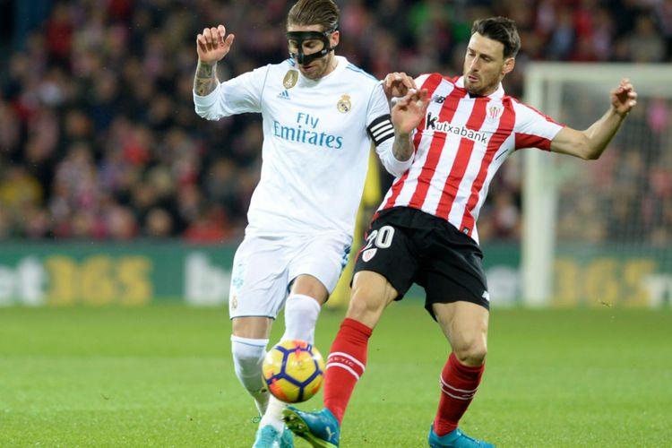 Sergio Ramos dan Aritz Aduriz berebut bola pada pertandingan La Liga antara Athletic Bilbao dan Real Madrid di San Mames, Sabtu (2/12/2017).