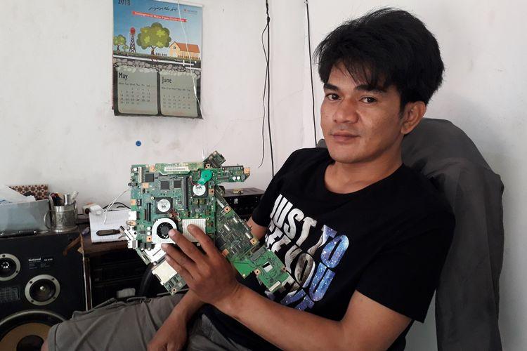 Shandra Ramadhan dan PCB sampah elektronik yang akan menjadi sumber emas baginya. Gambar diambil pada Rabu (30/5/2018).