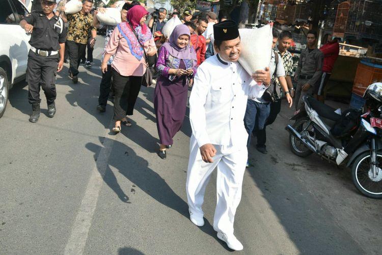 Bupati Purwakarta Dedi Mulyadi memanggul beras untuk dibagikan pada warga miskin di Purwakarta, Kamis (7/9/2017). Kegiatan membagikan beras pada masyarakat miskin merupakan perwujudan dari program Kemis Poe Welas Asih.