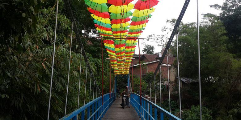 Seorang pengendara saat melintas di atas jembatan gantung di RT 6 RW 5 Kelurahan Penanggungan, Kecamatan Klojen, Kota Malang, Jawa Timur, Selasa (14/11/2017). Jembatan itu dihias dengan payung supaya kelihatan lebih indah.