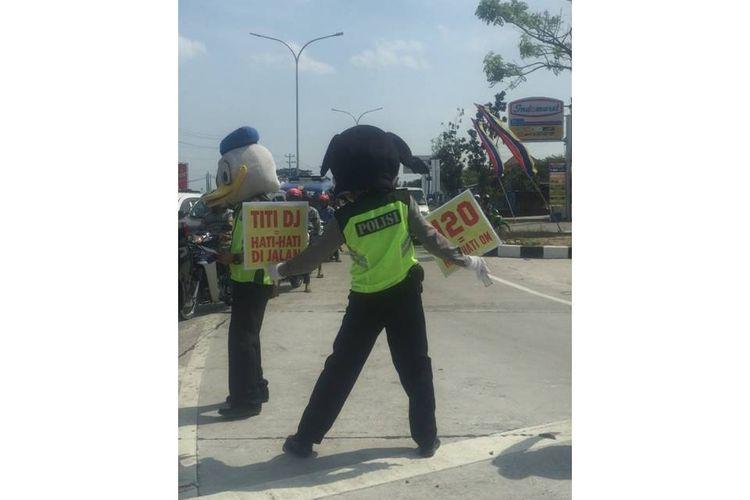 Dua polisi yang memakai topeng Mickey Mouse dan Donal Bebek berjoget menyapa para pengendara.