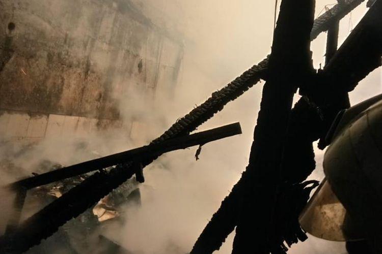 Kepulan asap saat petugas pemadam kebakaran berupaya menjinakkan api yang melalap rumah warga di Ciracas, Jakarta Timur, Selasa (18/6/2019).