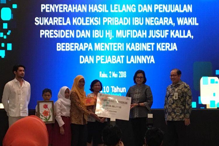 Menteri Keuangan Sri Mulyani Indrawati saat menyerahkan hasil lelang pejabat negara di gedung Jusuf Anwar, Kementerian Koordinator Bidang Perekonomian, Jakarta Pusat, Rabu (2/5/2018) malam.