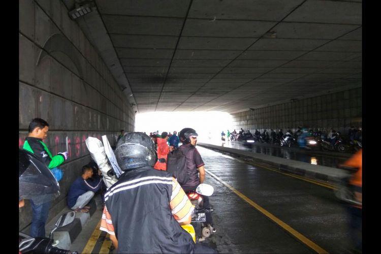 Para pengendara motor berteduh di kolong underpass Pasar Minggu Jakarta Selatan.