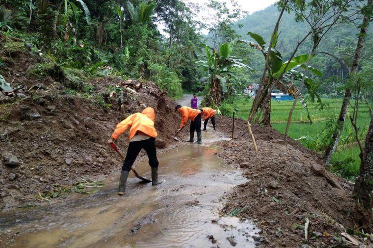 Personel Pusdalops BPBD Kabupaten Purbalingga menyingkirkan material longsor yang menutup  jalan penghubung Desa Kramat dan Sirau, Kecamatan Karangmoncol, Senin (16/10/2017).