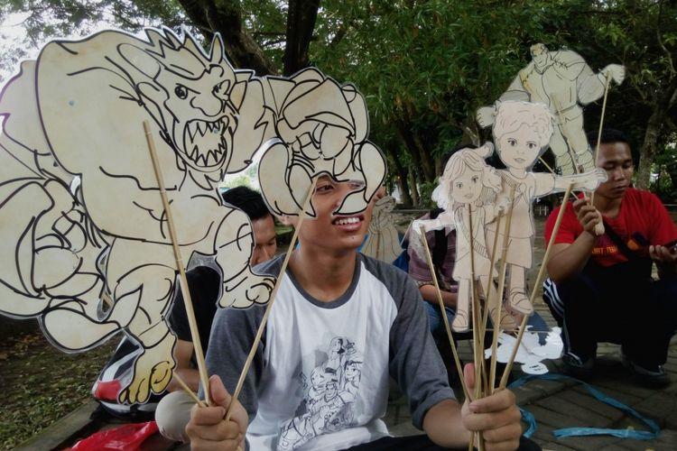 salah seirang relawan FCTC Mataram, mencoba sensasi memainkan wayang plastik atau wayang alternatif anti rokok, di Taman Udayana Mataram
