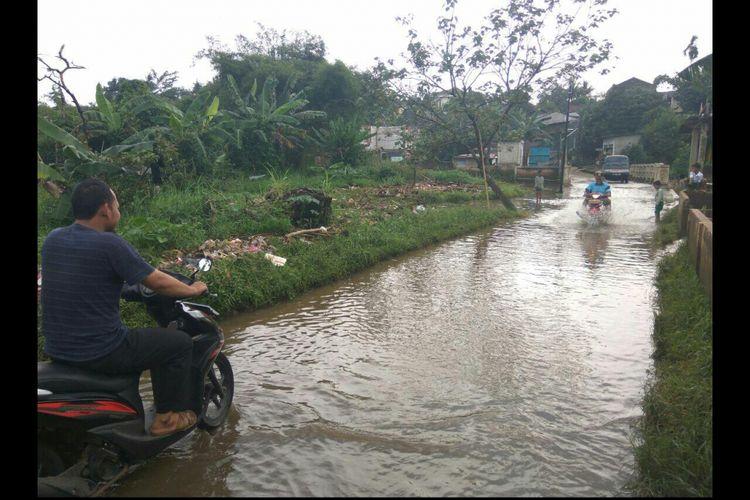 Sepeda motor mencoba melintasi Jalan Mawar RT 003 RW 004, Kelurahan Pasir Putih, Kecamatan Sawangan, Depok yang tergenang luapan air Kali Pesanggrahan, Rabu (14/2/2018).