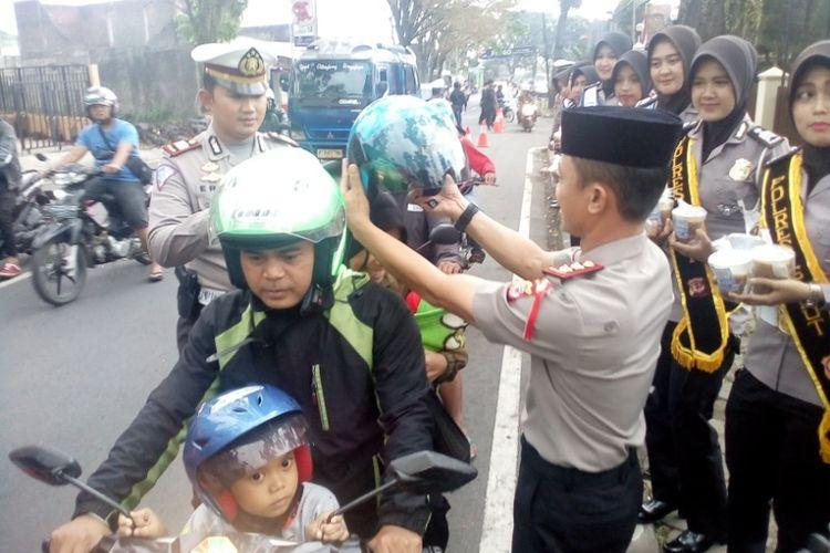 Kapolres Garut memasangkan helm kepada istri seorang pemotor yang melintas di depan Mapolres Garut, Kamis (17/5/2018).
