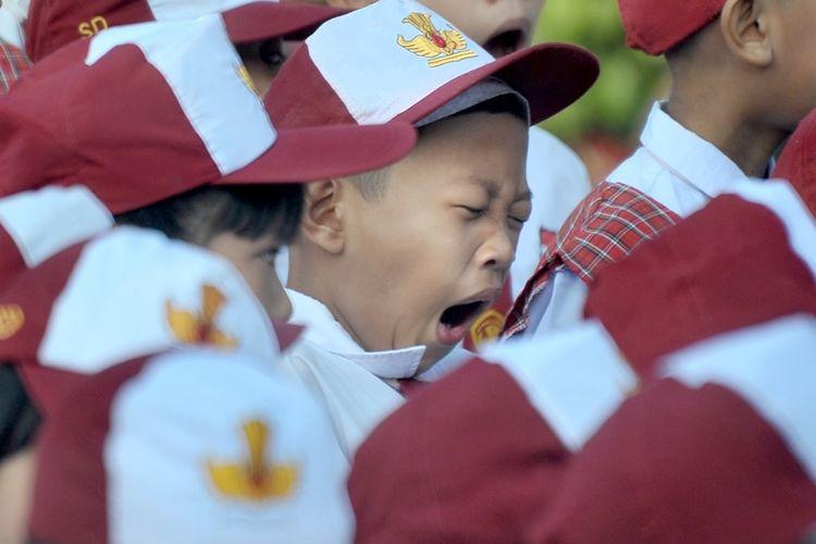 Salah satu siswa menguap di sela upacara bendera pada hari pertama masuk sekolah di Sekolah Dasar Negeri (SDN) 243 Palembang, Sumatera Selatan, Senin (16/7). Hari pertama masuk sekolah tahun ajaran 2018-2019 dimulai secara serentak di Indonesia pada Senin 16 Juli.