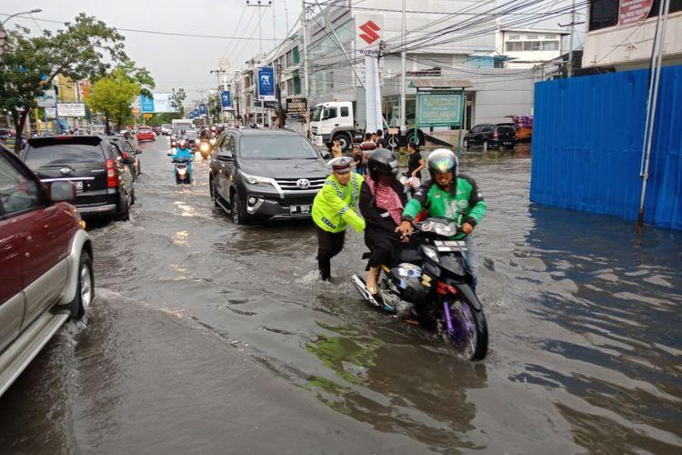 Polisi lalu lintas di pekanbaru membantu warga saat motornya mogok akibat genangan banjir