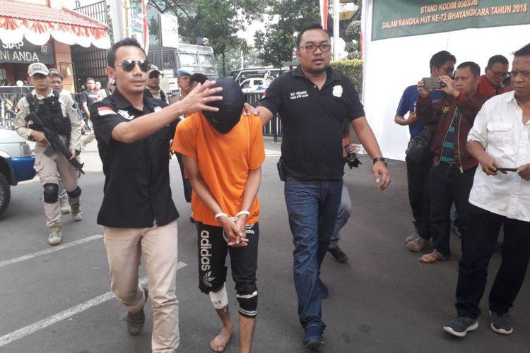 A, pelaku penjambretan terhadap Dirjen Bina Konstrukti Kemenpupera digiring polisi di Mapolres Metro Jakarta Barat, Jumat (29/6/2018).