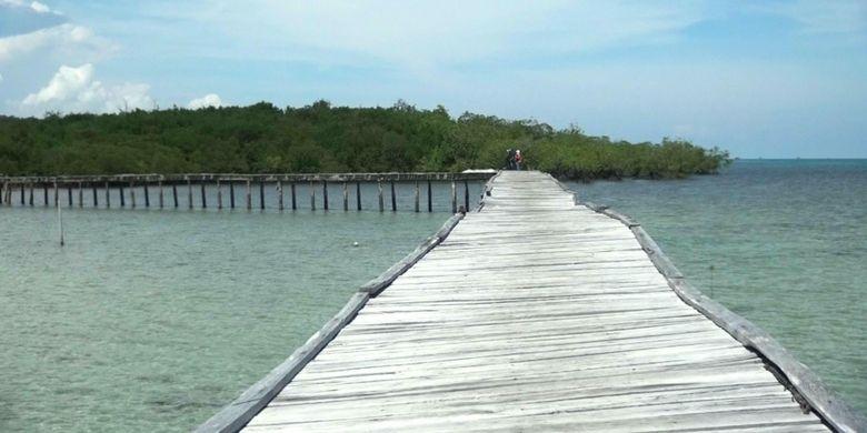 Jembatan kayu yang menghubungkan daratan Pulau Kelapan dengan dermaga kapal. Pulau Kelapan berada di Kabupaten Bangka Selatan, Kepulauan Bangka Belitung.