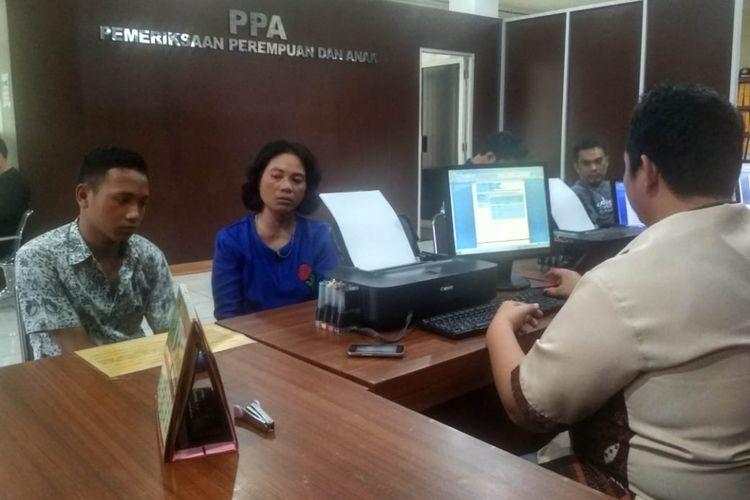 Suwandy (14) bersama ibunya, yang menjadi korban pengeroyokan oleh temannya sendiri saat melapor di Polresta Palembang, Jumat (21/9/2018). Suwandy menjadi korban pengeroyokan karena dituduh telah menghina pelaku inisial KR melalui Facebook.