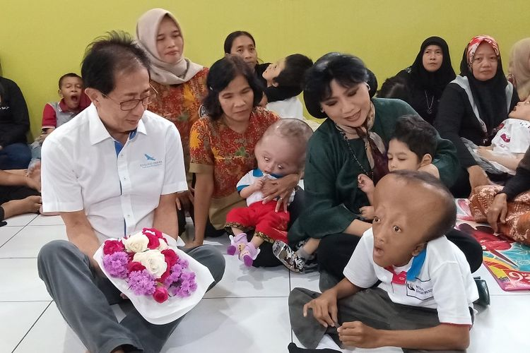 Direktur PT Berlico Mulia Farma Irwan Hidayat didampangi Pendiri Yayasan Wisma Kasih Bunda Anne Avantie mengunjungi anak-anak penderita hidrosefalus di Rumah Singgah Wisma Kasih Bunda, Semarang, Selasa (13/2/2019).