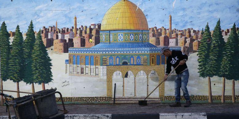 Seorang warga Palestina menyapu jalan pada 7 Desember 2017 di kota Hebron, di Tepi Barat yang diduduki Israel. Otoritas Palestina menyerukan demonstrasi mogok massal di kota Ramallah di Tepi Barat menyusul keputusan Presiden AS Donald Trump untuk mengakui Jerusalem sebagai ibu kota Israel.
