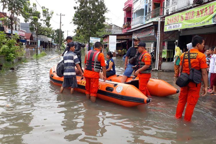Tim Basarnas Pekanbaru mengevakuasi warga yang dilanda banjir di wilayah Kecamatan Marpoyan Damai, Pekanbaru, Riau, Selasa (11/12/2018).